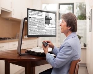 a woman using a desktop magnifier to read a newspaper