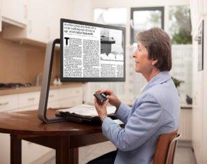 a woman using a desktop magnifier to read a newspaper